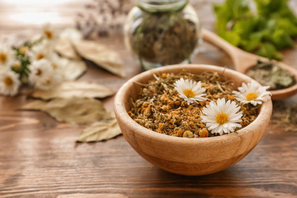 Bowl with dried chamomile flowers on wooden table